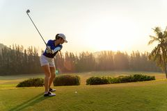 Asian woman golf player doing golf swing tee off on the green sunset evening time, she presumably does exercise. royalty free stock images
