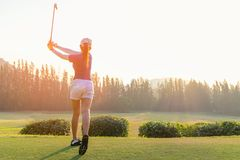 Asian woman golf player doing golf swing tee off on the green sunset evening time, she presumably does exercise. Healthy and Lifestyle Concept Stock Photos