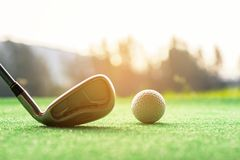 Asian woman Golf player hit swing shot golf ball on the green sunset eventing time. Royalty Free Stock Photos