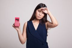 Asian woman got  headache with calculator. Royalty Free Stock Images