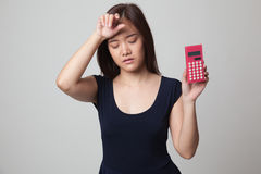 Asian woman got  headache with calculator. Royalty Free Stock Image