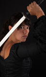 Asian woman grabbing her sword. Against a black background Royalty Free Stock Photo