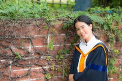 Asian woman in Graduate dress. In park stock photos