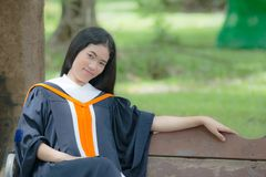 Asian woman in Graduate dress on bench. In park royalty free stock photography