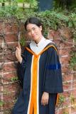 Asian woman in Graduate dress on brick wall. Smile Asian woman in Graduate dress on brick wall stock image