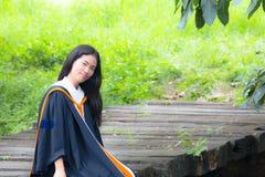 Asian woman in Graduate dress on bridge. Smile Asian woman in Graduate dress on bridge royalty free stock photo