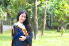 Asian woman in Graduate dress. In park royalty free stock image