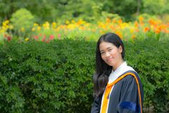 Asian woman in Graduate dress. In park stock images