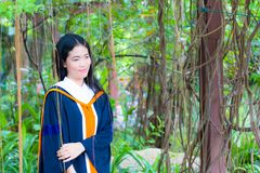 Asian woman in Graduate dress. In park royalty free stock images