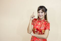 Asian woman greeting in traditional Chinese or cheongsam with hand lift welcome expression and lucky and finger pointing up in chi. Nese new year celebration in Stock Photos