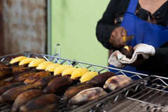 Asian woman grilled banana with hand holding knife in the market. In Thailand Royalty Free Stock Photos