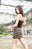 Asian woman with a gun in ruins Stock Photography