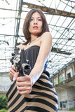 Asian woman with a gun in ruins Royalty Free Stock Photo