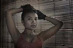 Asian woman in gym sport cloths looking with Venetian blinds window background Stock Photography