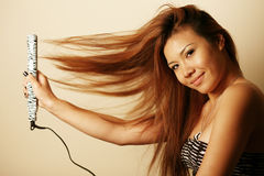 Asian woman with hair straightener Royalty Free Stock Photography