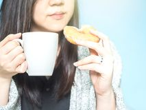 Asian woman hand with cloth hold the white coffee cup and eat do. Nut on morning time with blue pastel background Royalty Free Stock Image