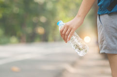 Asian woman hand hitchhiker holding bottle of water on nature ba Royalty Free Stock Photos