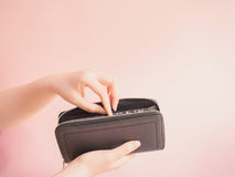 Asian woman hand hold and insert money in her blue purse with pi Stock Photos