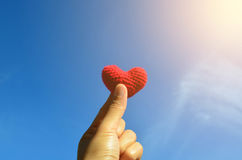 Asian woman hand hold red heart over blue sky and sun light Stock Image
