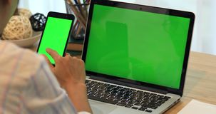 Asian woman hand holding cell phone.Phone and Laptop on desk with green screen. Asian woman hand is holding cell phone.Phone and Laptop on desk with green stock video footage