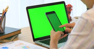 Asian woman hand holding cell phone.Phone and Laptop on desk with green screen. stock video footage