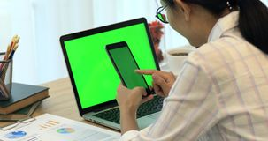 Asian woman hand holding cell phone.Phone and Laptop on desk with green screen. Asian woman hand is holding cell phone.Phone and Laptop on desk with green stock video