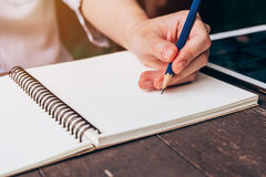 Asian woman hand writing pencil on notebook in coffee shop with. Vintage toned Royalty Free Stock Image
