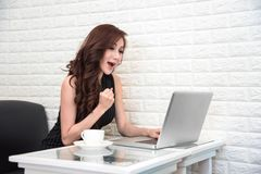 Asian woman happy after success new start up project or online bidding with laptop. Business and Success of people concept. royalty free stock photography