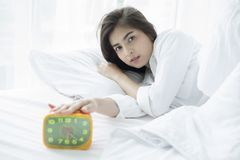 Asian woman happy waking up and turning off the alarm clock havi Royalty Free Stock Photography