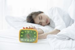 Asian woman happy waking up and turning off the alarm clock havi Stock Photography