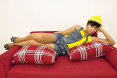 Asian woman with hard hat lies on red sofa Stock Photo