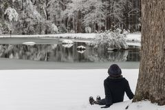 Asian woman in hat sitting in snow royalty free stock photos