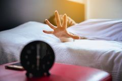 Asian woman hates getting stressed waking up early,Female stretching her hand to ringing alarm to turn off alarm clock Royalty Free Stock Images