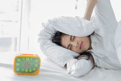 Asian woman hates waking up early in the morning. Sleepy girl lo. Oking at alarm clock and trying to hide under the pillow Royalty Free Stock Images