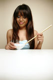 Asian woman hating her food. Asian woman not liking the food in her bowl stock image