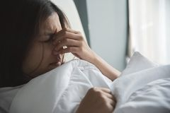 Asian woman having a cold. Girl having migraine on her bed. Illness, disease concept Stock Image
