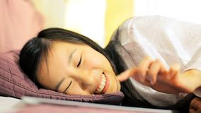 Asian woman having fun writing with tablet in bed Stock Photography