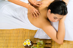 Asian woman having a massage in tropical setting Stock Images