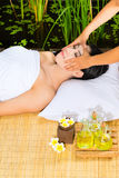 Asian woman having a massage in tropical setting Stock Photo