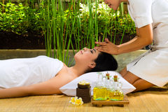 Asian woman having a massage in tropical setting Royalty Free Stock Images