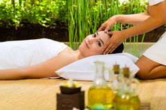 Asian woman having a massage in tropical setting Royalty Free Stock Photo