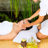 Asian woman having a massage in tropical setting Royalty Free Stock Image