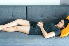 Asian woman having painful stomachache in bedroom after wake up,Female suffering from abdominal pain period cramps. Asian woman having painful stomachache in bed royalty free stock photos