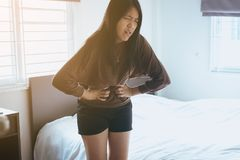 Asian woman having painful stomachache in bedroom after wake up,Female suffering from abdominal pain period cramps. Asian woman having painful stomachache in stock photography