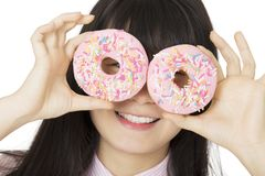 Asian woman having some fun with delicious strawberry frosted do. Playful Asian woman having some fun with delicious strawberry frosted donuts isolated on a Royalty Free Stock Image