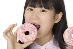 Asian woman having some fun with delicious strawberry frosted do. Playful Asian woman having some fun with delicious strawberry frosted donuts isolated on a Stock Image