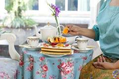 Asian  woman having  tea and cake and fresh fruit Stock Photography