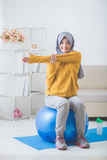 Asian woman with head scarf doing exercise at home Stock Image