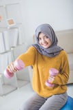 Asian woman with head scarf doing exercise at home Stock Images
