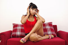 Asian woman with headphone sitting on red sofa Royalty Free Stock Images